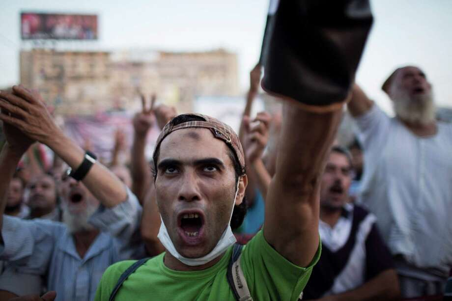 A supporter of Egypt's ousted President Mohammed Morsi chants slogans against Egyptian Army during a protest at the sit-in at Rabaa Al-Adawiya mosque, which is fortified with multiple walls of bricks, tires, metal barricades and sandbags, where protesters have installed their camp in Nasser City, Cairo, Egypt, Monday, Aug. 12, 2013. Security officials said police would besiege the entrenched protest camps within 24 hours — perhaps as early as Monday morning. (AP Photo/Manu Brabo) ORG XMIT: MB104 Photo: Manu Brabo / AP