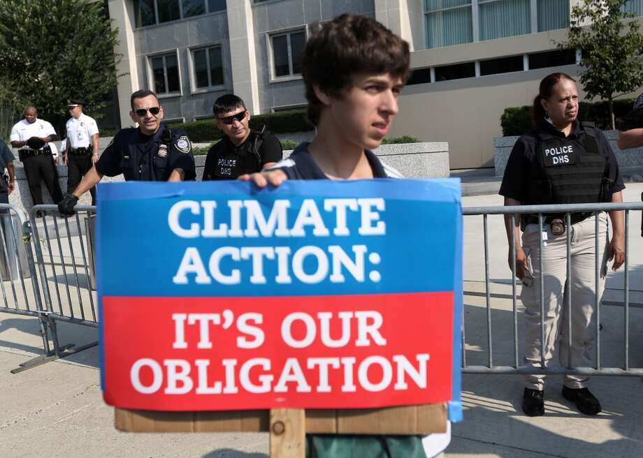 "An activist holds a sign as he participates in a sit-in and protest against the Keystone XL pipeline outside the U.S. State Department August 12, 2013 in Washington, DC. Activists from the Rainforest Action Network, CREDO and other groups expressed their opposition to the Keystone XL pipeline and urged ""to maintain pressure on the president to keep his promise to fight climate change by rejecting the Keystone XL pipeline."" Photo: Alex Wong, Getty Images"