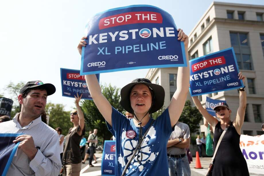 """Activists stage a sit-in and protest against the Keystone XL pipeline outside the U.S. State Department August 12, 2013 in Washington, DC. Activists from the Rainforest Action Network, CREDO and other groups expressed their opposition to the Keystone XL pipeline and urged """"to maintain pressure on the president to keep his promise to fight climate change by rejecting the Keystone XL pipeline."""" Photo: Alex Wong, Getty Images"""