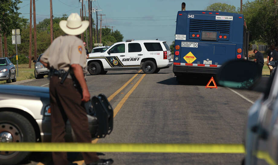 Law enforcement officers work the scene of a shooting Monday that took place on a VIA bus in Adkins. Photo: John Davenport, San Antonio Express-News