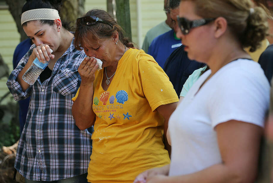 Gina Arellano, center, reacts as she and other flood-affected residents of Mission Road gather June 2 with members of Espada/Cabrini ACTS ministry for prayer. Photo: Jerry Lara / San Antonio Express-News