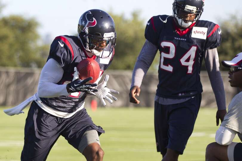 Cornerback Kareem Jackson (25) catches a ball during a drill with cornerback Johnathan Joseph (24).