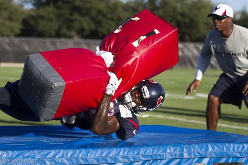 Cornerback Travis Howard hits a tackling dummy as defensive backs coach Vance Joseph, right, looks o