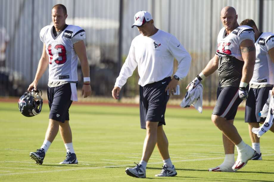 Quarterback T.J. Yates (13), offensive coordinator Rick Dennison and center Chris Myers (55) walk off the practice field. Photo: Brett Coomer, Chronicle