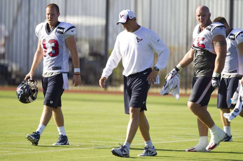 Quarterback T.J. Yates (13), offensive coordinator Rick Dennison and center Chris Myers (55) walk of