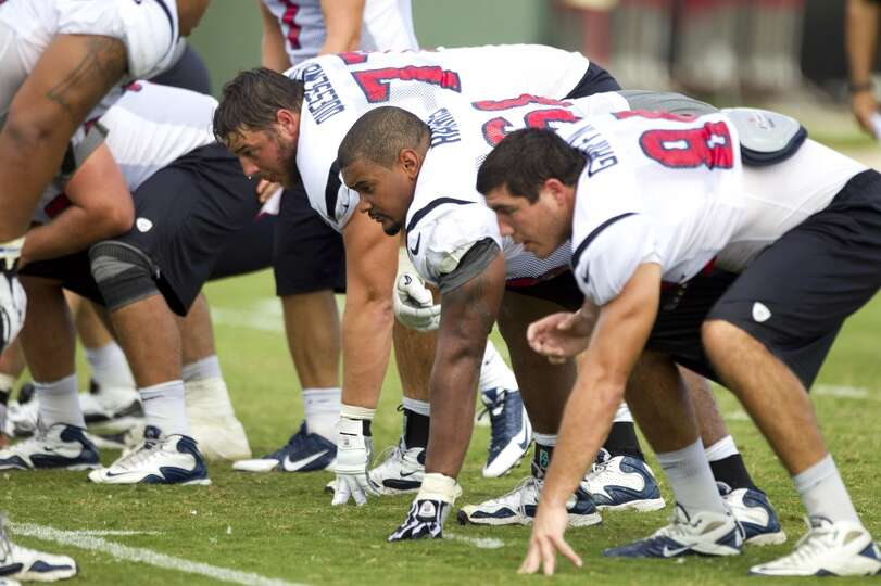 Offensive tackle David Quessenberry (77), tackle Ryan Harris (68) and tight end Ryan Griffin (84) li