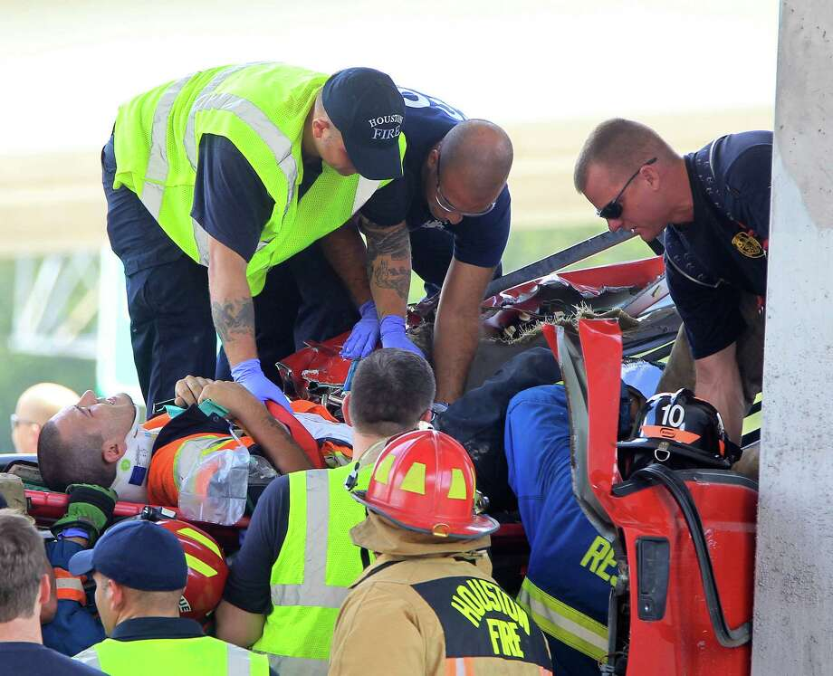 Houston Firefighters work to free a man trapped in a truck after an accident on the frontage road of I-59 north, inbound, Monday, Aug. 12, 2013, in Houston. The truck carrying three passengers apparently lost control on the frontage sending it into a concrete barrier killing one person, and sending two others, including the driver, to the hospital. Photo: Karen Warren, Houston Chronicle / © 2013 Houston Chronicle