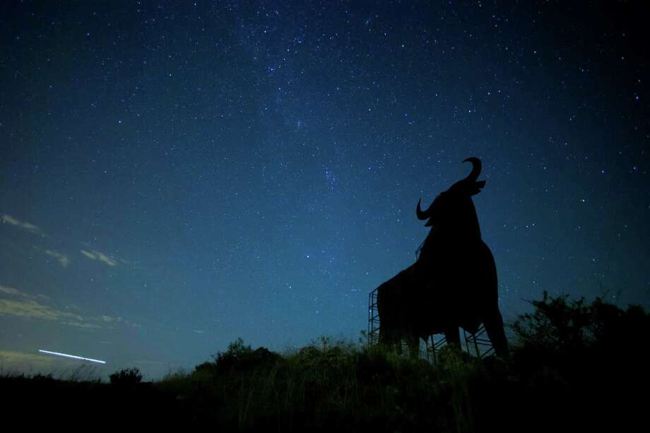 A Perseid meteor streaks across the sky during the annual Perseid meteor shower behind a roadside silhouette of a Spanish fighting bull, conceived decades ago in Spain as highway billboards, in Villarejo de Salvanes, central Spain in the early hours of Monday. Photo: AP