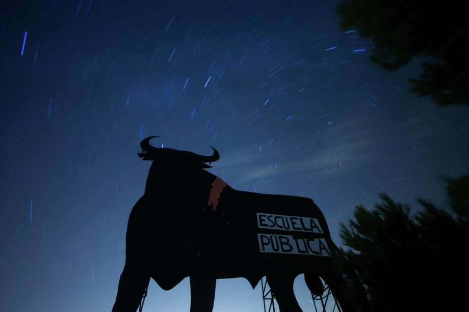 "Stars seen as streaks from a long camera exposure are seen behind and above a roadside silhouette of a Spanish fighting bull, conceived decades ago as highway billboards, in Villarejo de Salvanes, central Spain,  2013. A sign on the bull, put up by protesters, reads ""State schools"" as a reference for a demand for the state funded schools to continue. Photo: AP"