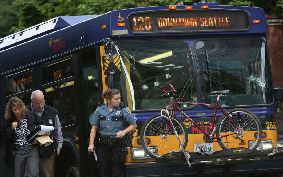 Investigators look over a bullet-riddled bus where a suspect was shot by  officers after the man shot a Metro driver. Seattle police shot the  suspect as he fled into a second bus during the morning rush hour.  Photographed on Monday, Aug. 12, 2013, in Seattle. Photo: JOSHUA TRUJILLO, SEATTLEPI.COM / SEATTLEPI.COM