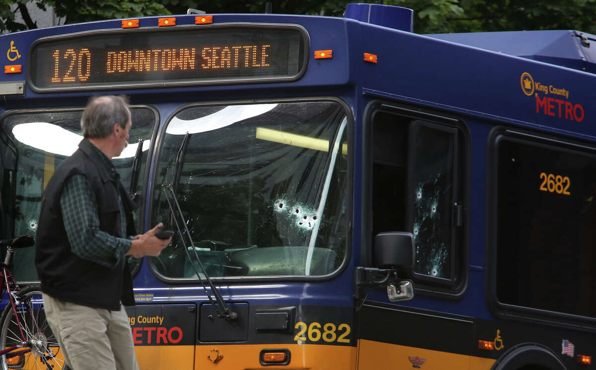 Investigators look over a bullet-riddled bus where a suspect was shot by officers after the man shot a Metro driver. Seattle police shot the suspect as he fled into a second bus during the morning rush hour. Photographed on Monday, Aug. 12, 2013, in Seattle.