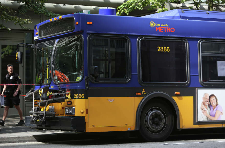 Investigators look over a bullet-riddled bus where a suspect was shot by