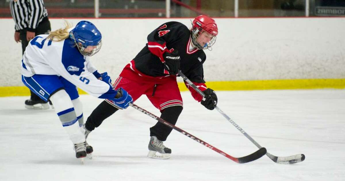 Darien's Perrin Brown, left, and New Canaan's Madzie Carroll, right, during a girls hockey game in Darien, Conn. on Wednesday, Jan. 20, 2010
