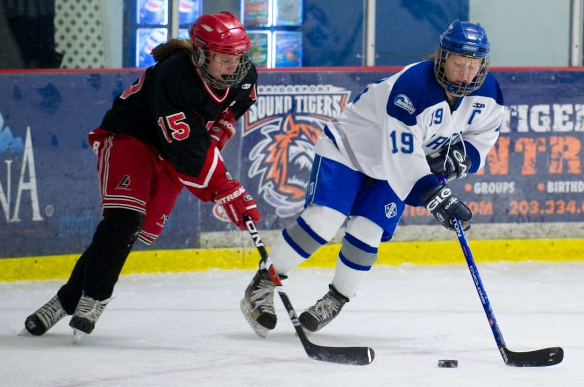 New Canaan's Jana Persky, left, and Darien's Madeline Coburn, right, during a girls hockey game in Darien, Conn. on Wednesday, Jan. 20, 2010