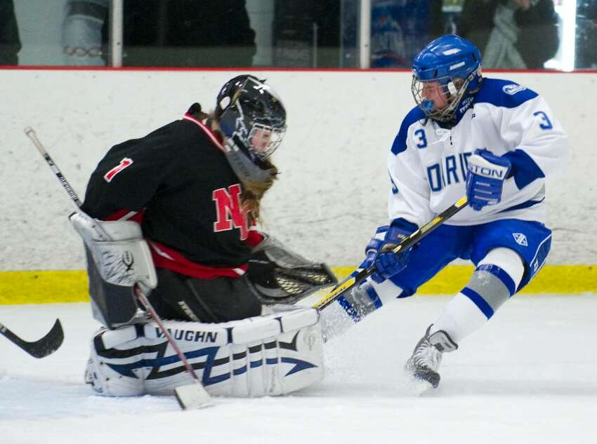Darien's Caroline Falcone, right, scores past New Canaan's Melissa Vitti, left, during a girls hockey game in Darien, Conn. on Wednesday, Jan. 20, 2010