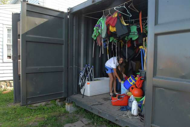 Camp Soundwaters director Lindsay Silbereisen puts away camp supplies on Monday August 12, 2013. Soundwaters is keeping camp gear, boating equipment and educational supplies that were in the basement and boat shed that were damaged in hurricane Sandy in storage containers outside the building in Stamford, Conn. Photo: Dru Nadler / Stamford Advocate Freelance