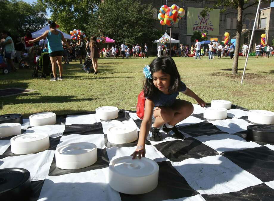 Celeste Medina, 7 plays checkers while at Kidcation Week Kickoff at Hemisfair Park on Monday Aug. 12, 2013. Photo: Helen L. Montoya, San Antonio Express-News / ©2013 San Antonio Express-News