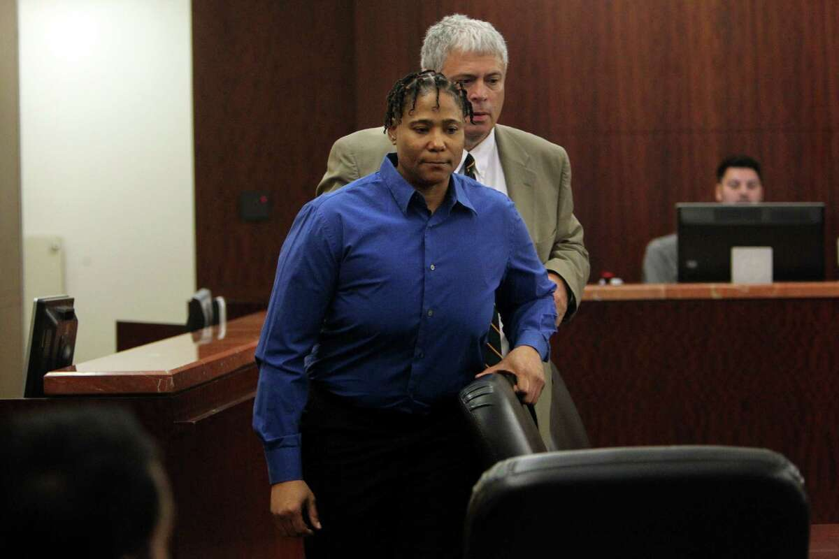 Mona Nelson, accused of killing 12-year-old Jonathan Foster, walks with defense attorney Allen Tanner in the courtroom for pretrial motions on Monday before beginning her capital murder trial this week on Monday, Aug. 12, 2013, in Houston.