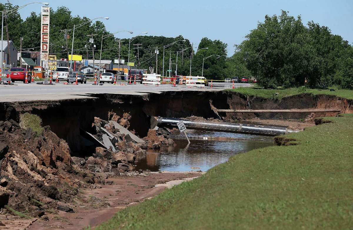 Flash flooding leaves a massive sinkhole on Route 62 June 2, 2013 in Oklahoma City, Oklahoma.