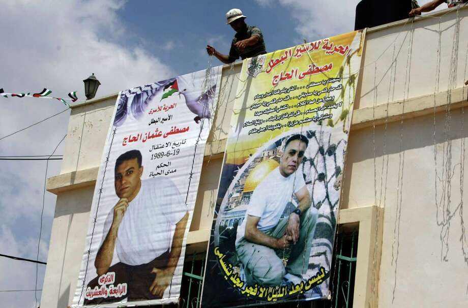 Banners of Mustafa al-Haj are put up Monday at the village of Brukin on the West Bank. Al-Haj is one of the 26 Palestinian prisoners to be released this week. Photo: Nasser Ishtayeh, STF / AP