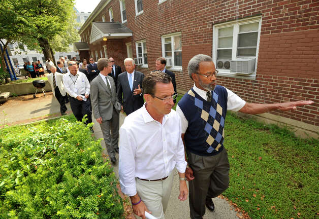 Gov. Dannel P. Malloy, front left, tours the Washington Village housing project with Executive Director of Norwalk Housing Authority Curtis Law in Norwalk, Conn., on Monday, Aug 12, 2013. First floor residents from Washington Village received flooding due to the storm surge from storm Sandy. Government officials are proposing to demolish the current dwellings and replace them with a housing project that is elevated above the flood level. Photo: Jason Rearick / Stamford Advocate