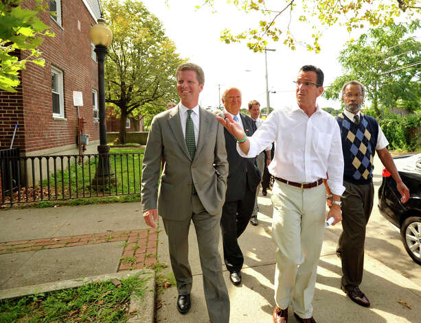 Secretary of Housing and Urban Development Shaun Donovan, left, and Gov. Dannel P. Malloy tour the Washington Village housing project in Norwalk, Conn., on Monday, Aug 12, 2013. First floor residents from Washington Village received flooding due to the storm surge from storm Sandy. Government officials are proposing to demolish the current dwellings and replace them with a housing project that is elevated above the flood level. Photo: Jason Rearick / Stamford Advocate