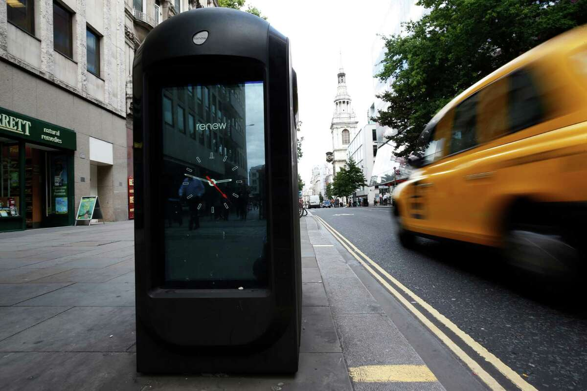 A taxi is driven past a trash bin in central London, Monday, Aug. 12, 2013. Officials say that an advertising firm must immediately stop using its network of high-tech trash cans, like this one, to track people walking through London's financial district.The City of London Corporation says it has demanded Renew pull the plug on the program, which measures the Wi-Fi signals emitted by smartphones to follow commuters as they pass the garbage cans. The City of London Corporation is responsible for the city's historic