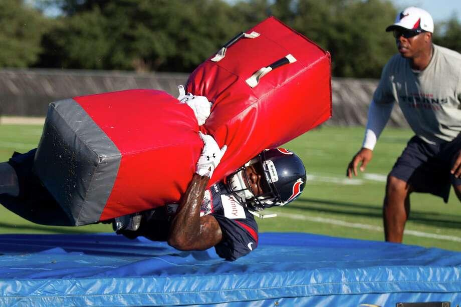 Houston Texans cornerback Travis Howard hits a tackling dummy as defensive backs coach Vance Joseph, right,  looks on during Texans training camp at the Methodist Training Center Monday, Aug. 12, 2013, in Houston.  ( Brett Coomer / Houston Chronicle ) Photo: Brett Coomer, Staff / © 2013 Houston Chronicle