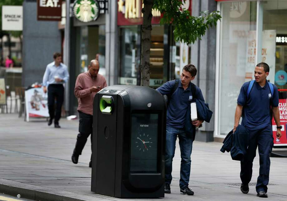A youth uses a trash bin in central London, Monday, Aug. 12, 2013. Officials say that an advertising firm must immediately stop using its network of high-tech trash cans, like this one, to track people walking through London's financial district. The City of London Corporation says it has demanded Renew pull the plug on the program, which measures the Wi-Fi signals emitted by smartphones to follow commuters as they pass the garbage cans.  (AP Photo/Lefteris Pitarakis) Photo: Lefteris Pitarakis, STF / AP