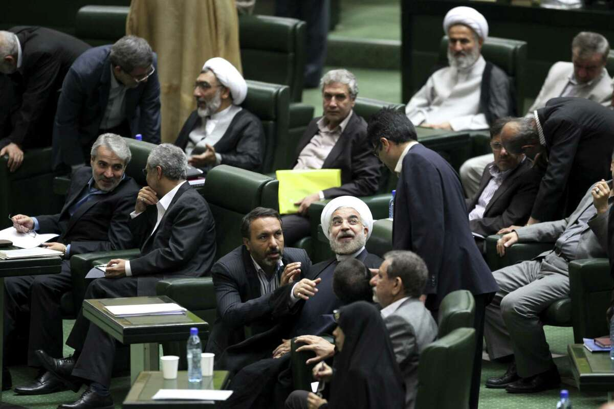 Iran President Hasan Rouhani (center) talks with lawmakers in a session of Parliament on Monday. Rouhani has pledged to improve an economy ravaged by international sanctions and mending fences with the rest of the world.