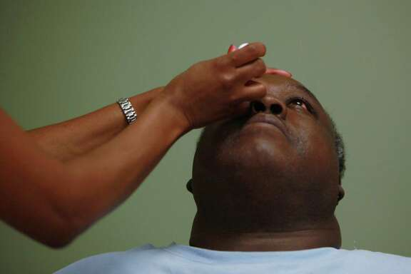 Diabetic patient Ronald Jones has his pupils dilated before his iris screening at the Harris Health System's Martin Luther King Jr. Health Clinic on Tuesday.