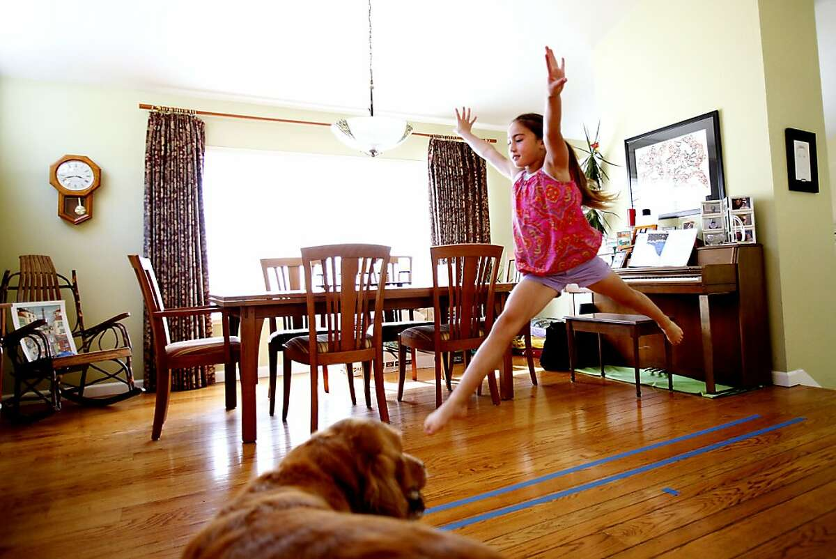 Madeleine Cunningham, 8, uses a balance beam taped on her floor to warm up for gymnastics class at home in Belmont, Calif., Monday, August 12, 2013. Madeleine was diagnosed with type one diabetes two years ago, and now must check her blood sugar about ten times a day. The California Supreme Court ruled that individuals other than registered nurses are now allowed to administer insulin injections at schools. Madeleine's parents are relieved, saying now they will worry less if her teacher is allowed to help with her insulin.