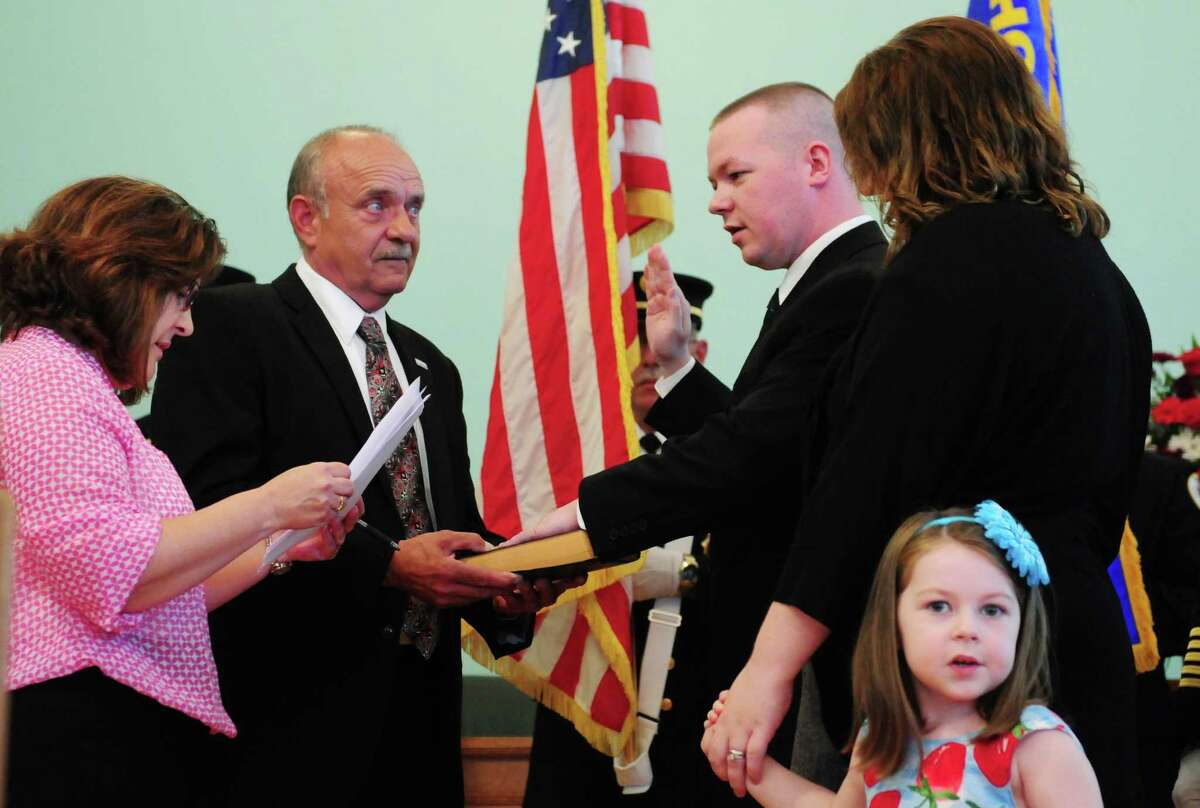 Peter Annely, center, was one of three new Cohoes firefighters to be sworn in by City Clerk Lori Yando, left, and Mayor George Primeau, Sr., second from left, Monday morning, Aug. 12, 2013, during a ceremony at City Hall in Cohoes, N.Y. Brian Bullock and Niklas Erickson were also sworn in. The three Cohoes residents will bring department staffing up to 32 firefighters. They will now head to Utica where they'll attend the firefighting academy. (Will Waldron/Times Union)