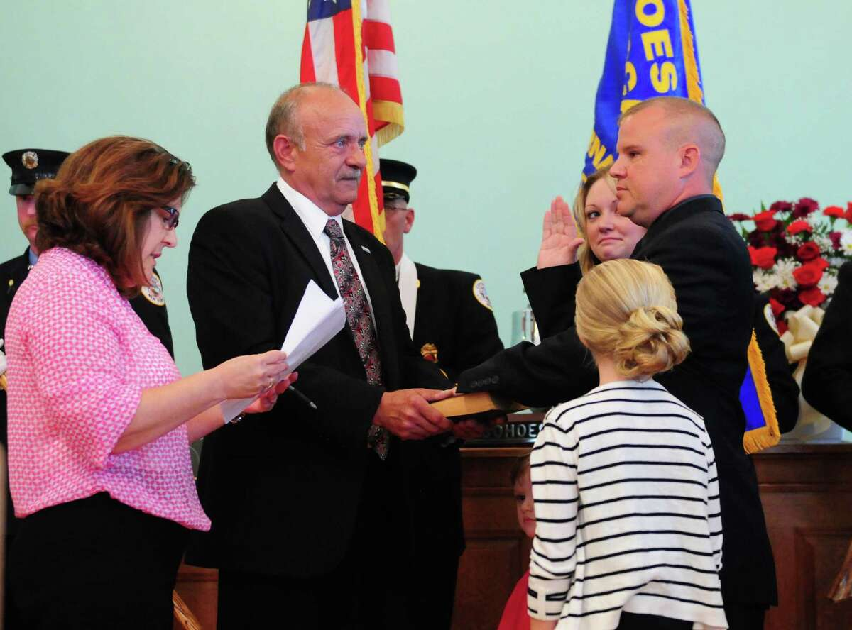 Brian Bullock, right, was one of three new Cohoes firefighters to be sworn in by City Clerk Lori Yando, left, and Mayor George Primeau, Sr., second from left, Monday morning, Aug. 12, 2013, during a ceremony at City Hall in Cohoes, N.Y. Peter Annely and Niklas Erickson were also sworn in. The three Cohoes residents will bring department staffing up to 32 firefighters. They will now head to Utica where they'll attend the firefighting academy. (Will Waldron/Times Union)