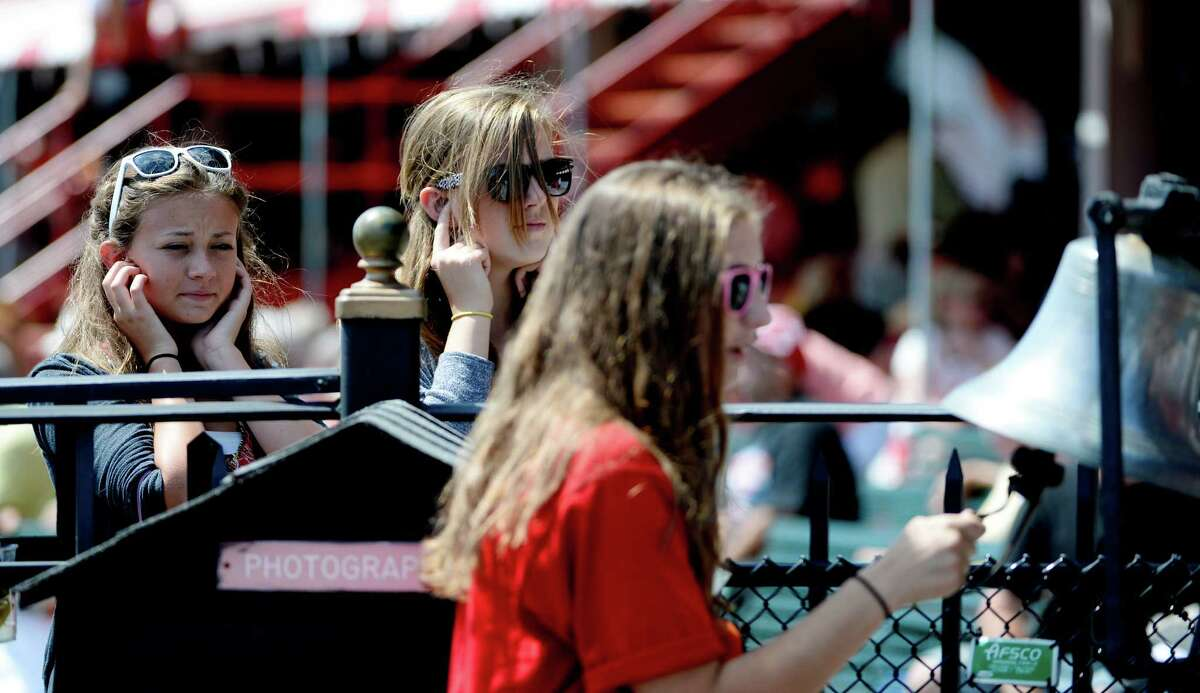 Julia Wales, 15, of Saratoga, left, and Laurel Griffen, 1,5 of Saratoga, center, cover their ears as Maggie Maydick, 15, of Saratoga rings the bell which announces the timing of 17 minutes to post Monday, Aug. 12, 2013, at the Saratoga Race Course in Saratoga Springs, N.Y. (Skip Dickstein/Times Union)