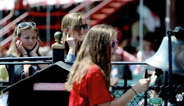 Julia Wales, 15, of Saratoga, left, and Laurel Griffen, 1,5 of Saratoga, center, cover their ears as Maggie Maydick, 15, of Saratoga rings the bell which announces the timing of 17 minutes to post Monday, Aug. 12, 2013, at the Saratoga Race Course in Saratoga Springs, N.Y.   (Skip Dickstein/Times Union) Photo: SKIP DICKSTEIN