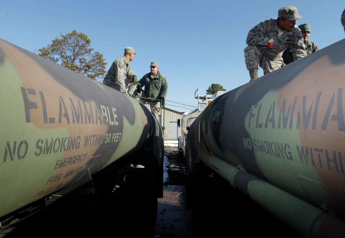 Army and Air National Guardsmen work on top of military tanker trucks in Freehold, N.J., Friday, Nov. 9, 2012, as they load fuel for delivery. Guard units have been deployed to help as the region continues to recover from last week's pounding by Superstorm Sandy. (AP Photo/Mel Evans)