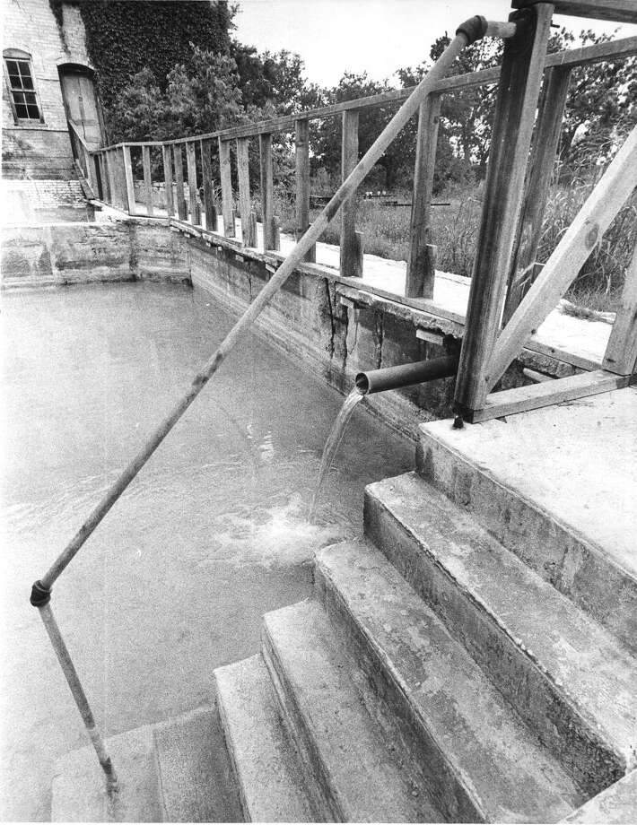 Sulphur Water which is a continuosly 105 degrees pours out of a pipe in the wall into one of the pools in the back of the Hot Wells Hotel. Photo: Files, San Antonio Express-News File Photo / SAN ANTONIO EXPRESS-NEWS
