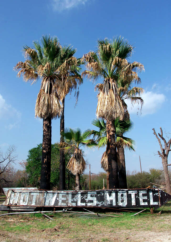 View of the Hot Wells Hotel signage leaning against palm trees. Photo: Kin Man Hui, San Antonio Express-News / SAN ANTONIO EXPRESS-NEWS