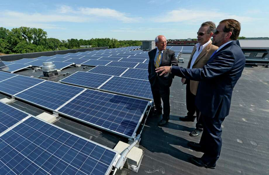 Steve Erby, VP, right, and Mark Fobare president, center, of Monolith Solar Associates shows Congressman Paul Tonko the newly installed solar modules at the two-story, 42,000 square foot building located on Patroon Creek Boulevard Aug. 12, 2013, in Albany, N.Y.  The energy supply generated by this building is said to supply enough power for approximately 25 homes for an entire year. This system is rated at 100,800 watts and features a total of 360 modules on the roof. The annual production at this location is estimated at approximately 120,960 kWh's per year.   (Skip Dickstein/Times Union) Photo: SKIP DICKSTEIN / 00023480A