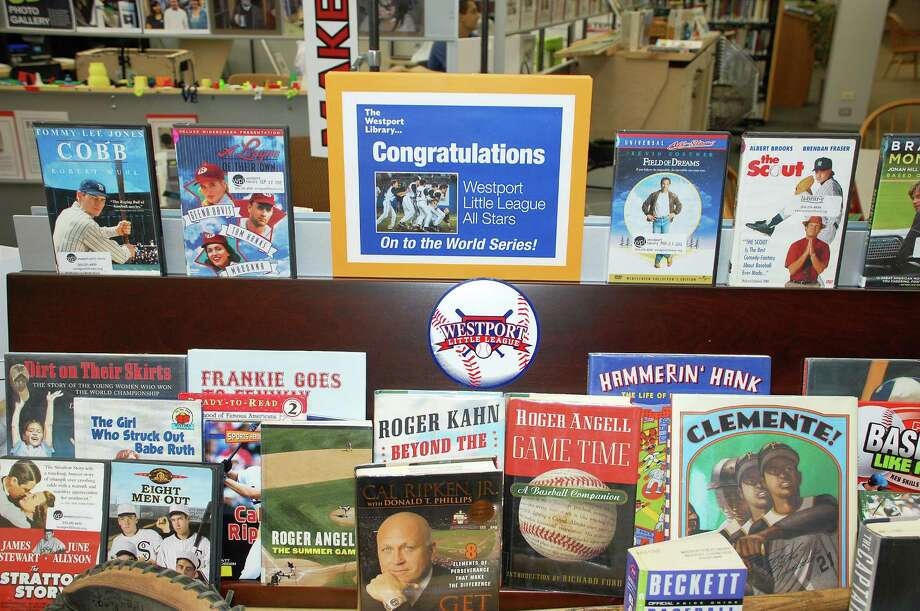 A baseball-themed display of books and memorabilia has been set up at the Westport Library in preparation for the Westport Little League team's games in the Little League World Series. The library will host a public viewing of the team's first game in the tourney on its big-screen television at 7 p.m. Thursday in the McManus Room. Photo: Jarret Liotta / Westport News contributed