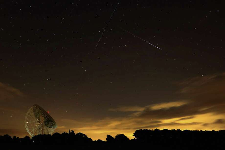 A Perseid meteor streaks across the sky over the Lovell Radio Telescope at Jodrell Bank on Tuesday in Holmes Chapel, United Kingdom.The annual display, known as the Perseid shower because the meteors appear to radiate from the constellation Perseus in the northeastern sky, is a result of Earth's orbit passing through debris from the comet Swift-Tuttle. Photo: Christopher Furlong, Getty / 2013 Getty Images
