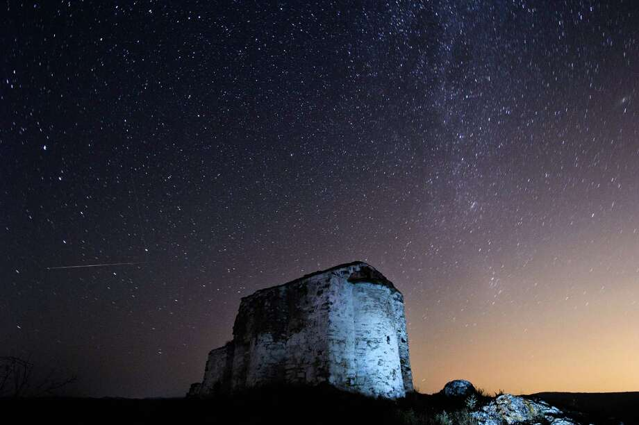 A long-exposure image showing a Perseids meteor (L) streaking across the night sky over St. Ioan medieval church near the village of Potsurnentsi, Bulgaria, late on Monday. The Perseid meteor shower occurs every year in August when the Earth passes through the debris and dust of the Swift-Tuttle comet. Photo: DIMITAR DILKOFF, Getty / 2013 AFP