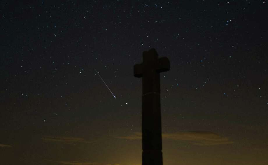 A meteor streaks across the night sky above New Ralph's Cross on Tuesday on the North Yorkshire Moors, United Kingdom. The Perseid Meteor shower is visible from mid-july each year with peak activity being between the 9th and 14th of August. During the peak, the rate of meteors can reach 60 or more per hour. They can be seen all across the sky as they gradually fall away from the tail of the Swift-Tuttle comet. Photo: Ian Forsyth, Getty / 2013 Ian Forsyth