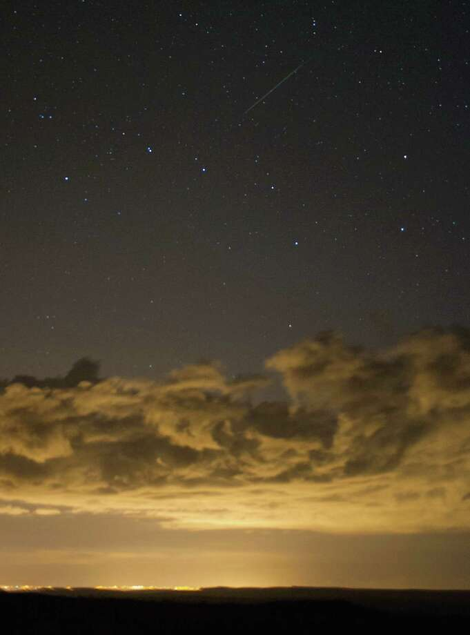 A meteor is visible as it streaks across the night sky and appearing to be above the constellation of Ursa Major on Tuesday over the North Yorkshire Moors, United Kingdom. The Perseid Meteor shower is visible from mid-july each year with peak activity being between the 9th and 14th of August. During the peak, the rate of meteors can reach 60 or more per hour. They can be seen all across the sky as they gradually fall away from the tail of the Swift-Tuttle comet. Photo: Ian Forsyth, Getty / 2013 Ian Forsyth