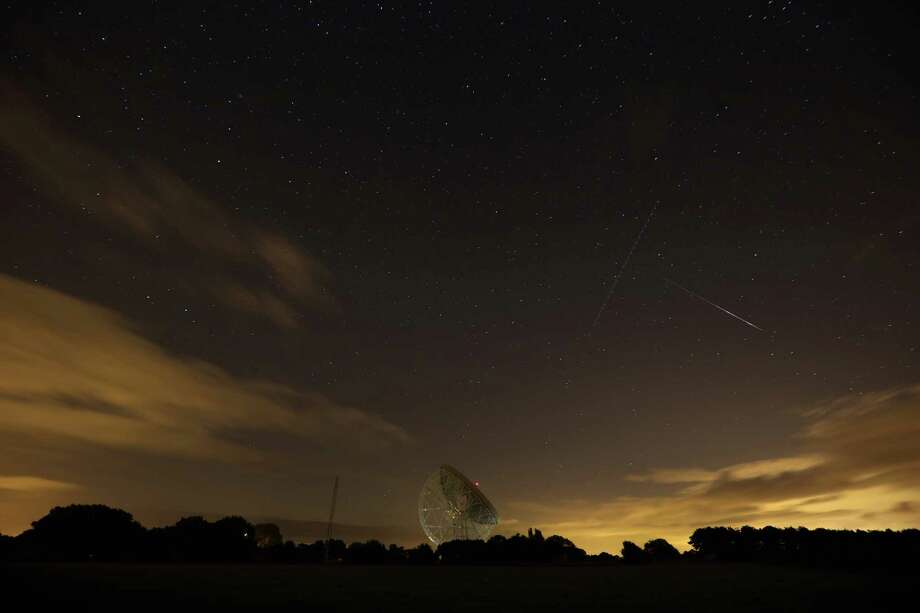 A Perseid meteor (R) streaks across the sky past the light trail of an aircraft over the Lovell Radio Telescope at Jodrell Bank on Tuesday  in Holmes Chapel, United Kingdom.The annual display, known as the Perseid shower because the meteors appear to radiate from the constellation Perseus in the northeastern sky, is a result of Earth's orbit passing through debris from the comet Swift-Tuttle. Photo: Christopher Furlong, Getty / 2013 Getty Images