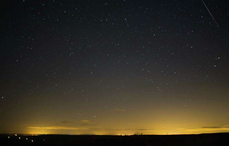 A meteor (top right) streaks across the night sky on Tuesday over the North Yorkshire Moors, United Kingdom. The Perseid Meteor shower is visible from mid-july each year with peak activity being between the 9th and 14th of August. During the peak, the rate of meteors can reach 60 or more per hour. They can be seen all across the sky as they gradually fall away from the tail of the Swift-Tuttle comet. Photo: Ian Forsyth, Getty / 2013 Ian Forsyth