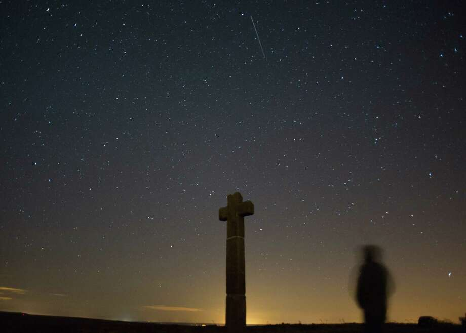 James Ritson looks skywards as a meteor streaks across the night sky above New Ralph's Cross on Tueday over the North Yorkshire Moors, United Kingdom. The Perseid Meteor shower is visible from mid-july each year with peak activity being between the 9th and 14th of August. During the peak, the rate of meteors can reach 60 or more per hour. They can be seen all across the sky as they gradually fall away from the tail of the Swift-Tuttle comet. Photo: Ian Forsyth, Getty / 2013 Ian Forsyth