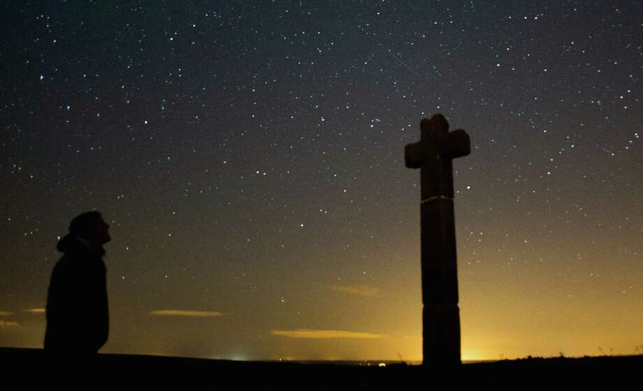 James Ritson looks skywards as a meteor streaks across the night sky above New Ralph's Cross on Tuesday over the North Yorkshire Moors, United Kingdom. The Perseid Meteor shower is visible from mid-july each year with peak activity being between the 9th and 14th of August. During the peak, the rate of meteors can reach 60 or more per hour. They can be seen all across the sky as they gradually fall away from the tail of the Swift-Tuttle comet. Photo: Ian Forsyth, Getty / 2013 Ian Forsyth