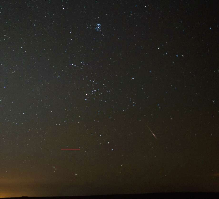 A meteor (bottom right) streaks across the night sky on Tuesday over the North Yorkshire Moors, United Kingdom. A commercial aircraft (bottom left) can also be seen as can the constellation of Pleiades (top). The Perseid Meteor shower is visible from mid-july each year with peak activity being between the 9th and 14th of August. During the peak, the rate of meteors can reach 60 or more per hour. They can be seen all across the sky as they gradually fall away from the tail of the Swift-Tuttle comet. Photo: Ian Forsyth, Getty / 2013 Ian Forsyth